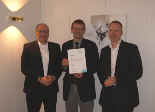 Bild: Frank Müller (links) von der Fa. KYOCERA und Andreas Blomberg (rechts) von der Fa. Büscher überreichen Fachbereichsleiter Detlef Slotta (Mitte) die CO2-Kompensationsurkunde