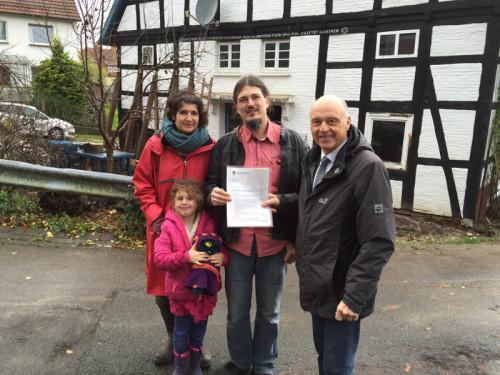 """Blomberg-Reelkirchen. Bürgermeister Klaus Geise (r.) übergibt Familie Bruns vor ihrem neuen Zuhause den ersten Förderbescheid aus dem Programm """"Jung kauft alt"""""""