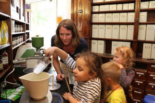 Vorsichtig wird Gramm für Gramm abgemessen – Apothekerin Tina Hillemeier zeigt Lea (6) wie Tee aus Heilkräutern gemischt wird.