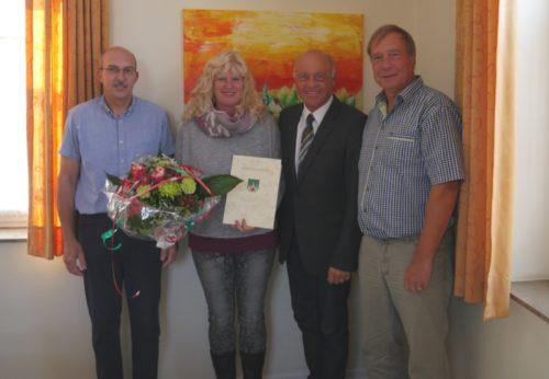 Bürgermeister Klaus Geise (2.v.rechts), Teamleiter Uwe Praschak (rechts) und Personalratsvorsitzender Winfried Kipke (links)  gratulieren Nicole Prokisch zum 25jährigen Dienstjubiläum bei der Stadt Blomberg