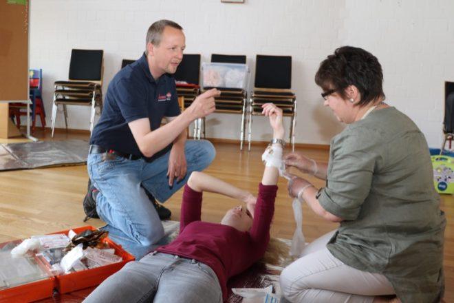 Jeder Teilnehmer muss Hand anlegen - Ausbilder Jens Hollmann von den Johannitern zeigt das richtige Anlegen eines Druckverbandes.