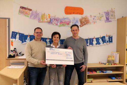 Leiterin der Kita Regenbogen, Marion Gurcke, nimmt freudenstrahlend den Spendenscheck entgegen, überreicht von den Vettern Christian Schlüter (l.) und Tobias Weber.